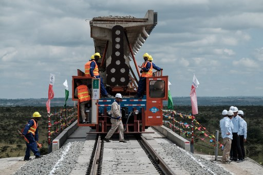 Workers move a track at the construction site of Standard Gauge Railway near Nairobi, Kenya