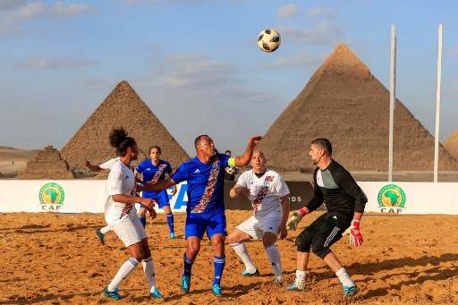 Brazilian footballer Cafu (C) and French football player Laura Georges (L) vie for the ball during the CAF and FIFA Legends football match, part of the CAF celebration of the best players in Africa, at the Giza pyramids plateau on the southwestern outskirts of the Egyptian capital Cairo on January 6, 2020.
