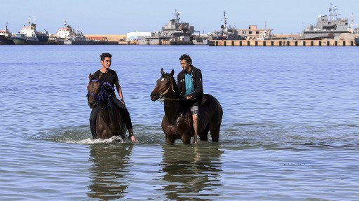 Two Libyan horse owners cool their horses in the sea in the Tripoli area on May 5th. Adherence to a COVID-19 lockdown has been sporadic.