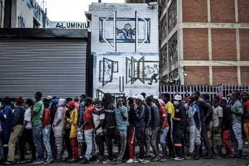 People queue to receive food during a distribution organised by the local Muslim organisation Ghous-e-aazam Welfare, in the Kwa Mai Mai area of the Johannesburg CBD, on May 5, 2020 as the country fight against the spread of the COVID-19, t