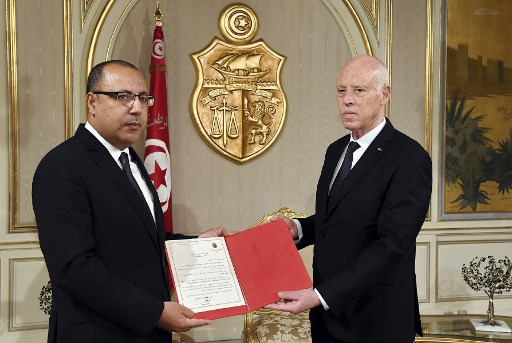 In this handout picture provided by the Tunisian Presidency Press Service, Tunisian president Kais Saied (R) appoints Interior Minister Hichem Mechichi as the country's new prime minister, tasked with forming a new unity cabinet, at the Carthage Palace on the eastern outskirts of the capital Tunis on July 25, 2020. (Tunisian Presidency/AFP)