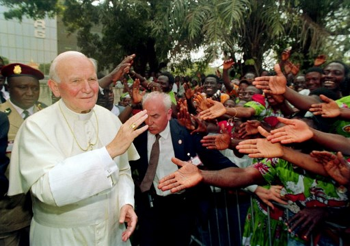 Pope John Paul II greets out-stretched hands during a walk-about 24 February 1992 in Conakry. The pontiff visited Senegal, Gambia and Guinea from 19 to 26 February. It was his 54th International Pastoral visit. Photo By MICHEL GANGNE / AFP