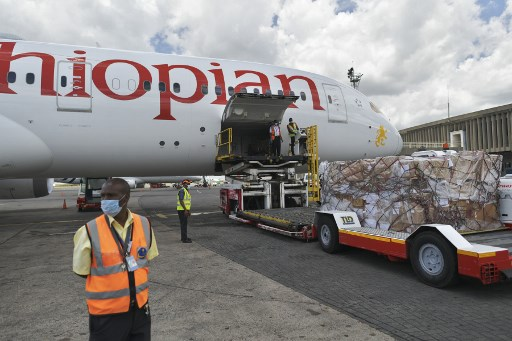 A consignment of masks, testing kits and protective gear, a donation from the Chinese billionaire and Alibaba co-founder Jack Ma, are unloaded from a cargo plane operated by Ethiopian airlines on March 24, 2020 after it arrived at the Jomo Kenyatta airport in Nairobi to help enhance capacity at the COVID-19 coronavirus infection testing centres in Kenya. As the global pandemic takes root in Africa, Chinese billionaire Jack Ma announced he was donating 20,000 testing kits, 100,000 masks and 1,000 protective suits to each of the continent's 54 countries TONY KARUMBA / AFP