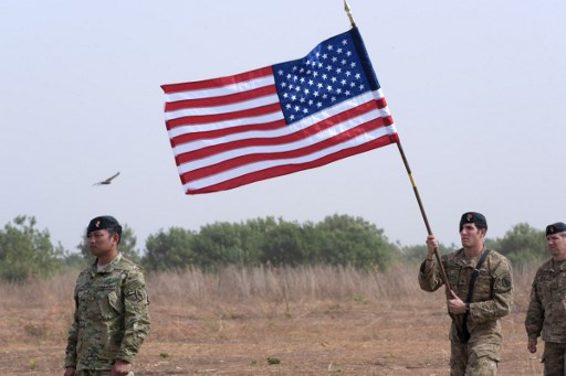 A soldier carries the USA national flag during the inauguration of a military base in Thies, 70 km from Dakar, on February 8, 2016 on the second day of a three-week joint military exercise between African, US and European troops, known as Flintlock. Some 1,700 members of the special forces from nearly thirty countries from Africa, America and Europe, including France and Britain, are taking part in military exercises from February 8-29 according to AFRICOM, the military command of the USA for Africa. SEYLLOU / AFP