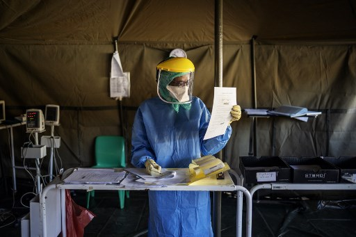 A health worker fills out documents before performing tests for COVID-19 coronavirus on other health workers at the screening and testing tents set up at the Charlotte Maxeke Hospital in Johannesburg, on April 15, 2020. Michele Spatari / AFP