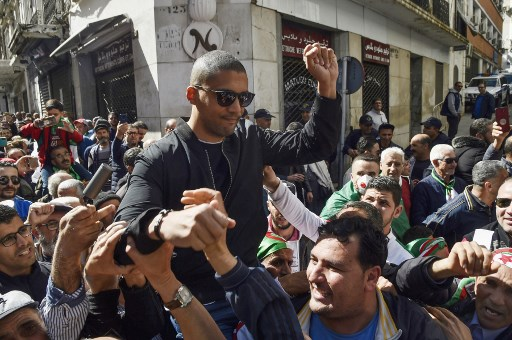 "A picture taken on March 6, 2020 shows Algerian protesters carrying journalist Khaled Drareni on their shoulders after he was briefly detained by security forces in the Algerian capital Algiers. Drareni was arrested on March 7 while covering an anti-government protest, accused of ""inciting an unarmed gathering and damaging national integrity"". RYAD KRAMDI / AFP"
