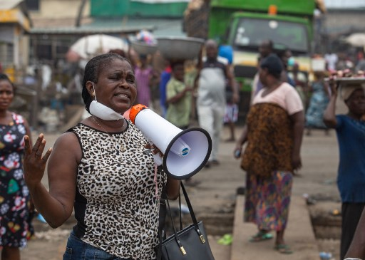 An activist uses a megaphone to address members of the public on the importance of social distancing in Accra, Ghana. April 4th 2020. Ghana has announced a two-week lockdown in the country's two main regions of Accra and Kumasi. The move came as the authorities reported 137 confirmed cases, including four deaths. Nipah Dennis / AFP