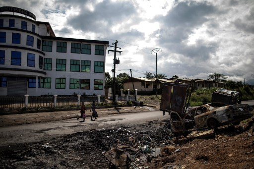 Women pass by the edge of the abandoned market into the majority anglophone South West province in Buea