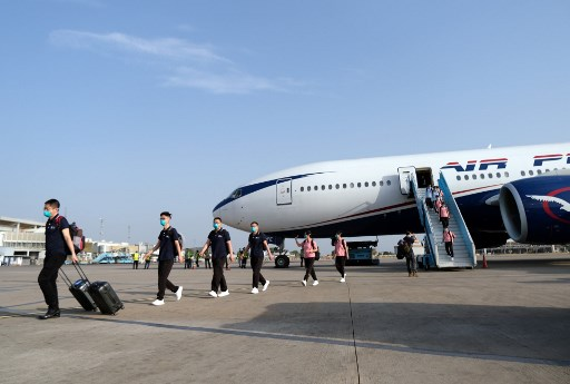Chinese medics disembark from a plane at the Nnamdi Azikwe International Airport in Abuja, on April 8, 2020 as they arrived in Nigeria to help fight the coronavirus pandemic, despite angry criticism from health workers in the west African nation. The 15-strong team were greeted by senior officials on the tarmac at Abuja airport after flying in on a month-long deployment with a planeload of medical supplies. Kola Sulaimon / AFP
