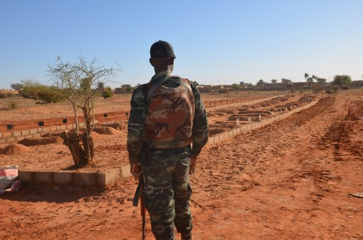 A Niger soldier looks at the graves of the soldiers killed before the arrival of the Leaders of the G5 Sahel nations in Niamey, on December 15, 2019. Leaders of the G5 Sahel nations paid homage at the graves of 71 Niger military personnel killed in a jihadist attack on December 10, 2019, ahead of a regional summit to coordinate a response to the growing unrest.  Boureima HAMA / AFP