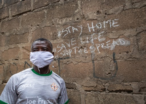 Steven, a bag seller, poses for a photograph by a wall close to his shop after the partial lockdown in parts of Ghana to halt the spread of the COVID-19 coronavirus was lifted in Accra, Ghana on April 20, 2020. The streets of Accra buzzed with life following President Nana Akufo-Addo's announcement of the end to a three-week restriction on movement around the capital and second region Kumasi. Nipah Dennis / AFP