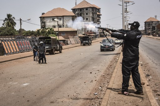 A policeman fires tear gas during clashes with protesters in the opposition stronghold of Wanindara, a northern suburb of Conakry, on February 27, 2020. Guinea is holding a referendum on March 1, 2020, on whether to change the constitution, which could allow the incumbent president to run for a third term this year. Guineans have demonstrated en masse against the possibility since mid-October, in protests where at least thirty protesters and one gendarme have been killed, according to an AFP tally. CELLOU BINANI / AFP