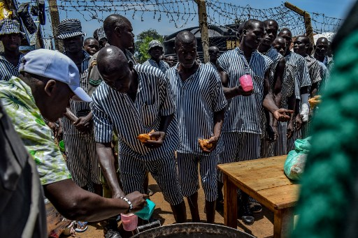 Inmates stand in a queue as they are served tea and fried dough bread (locally known as mandazi) during a talent show at the medium security section of Kodiaga Prison in the lakeside city of Kisumu on March 31, 2019.