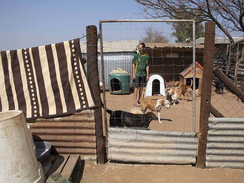 Kosmos, Tshwane. Some of the residents are in charge of feeding the dogs, cleaning them and making them play. ©Manash Das.