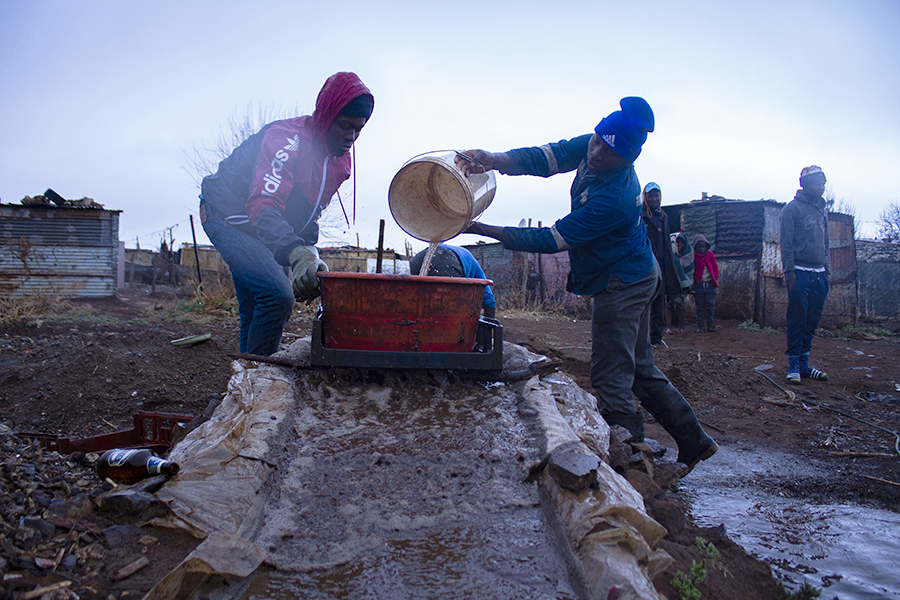 Xawela, Carletonville. Young manpower working tirelessly under a heavy rain. ©Manash Das.