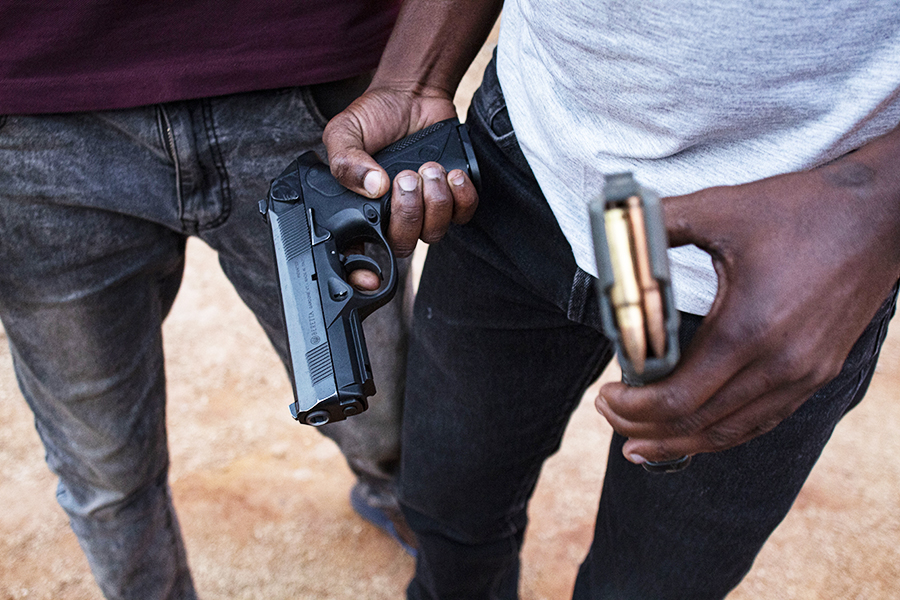 Khutsong, Carletonville. A gangster showing off his arsenal. ©Manash Das.