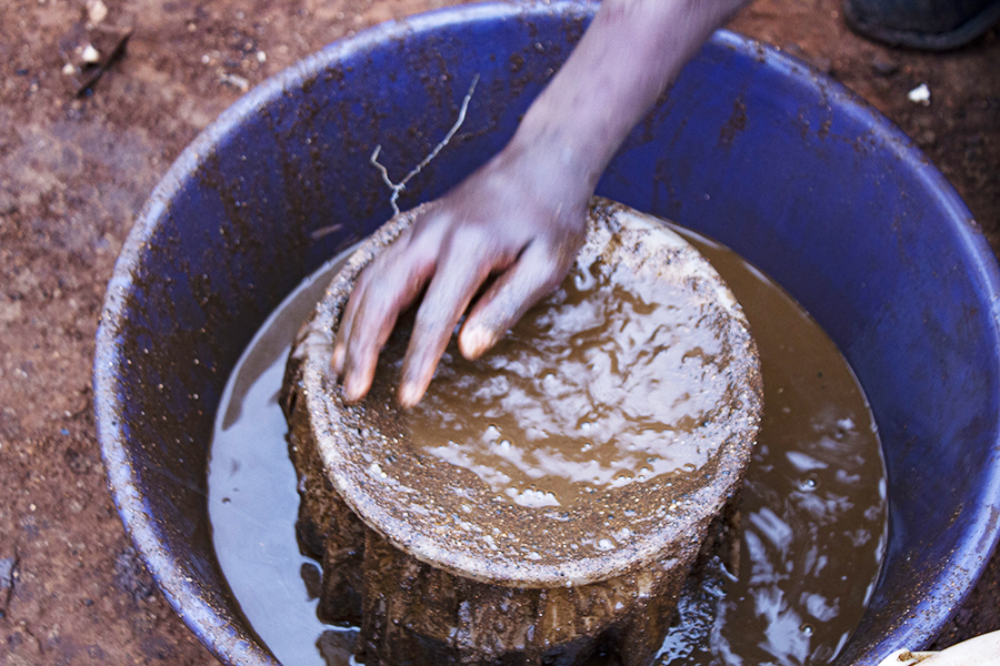 Xawela, Carletonville. Once the cloths are full of gold dust, John D washes them carefully in a bucket. ©Manash Das.