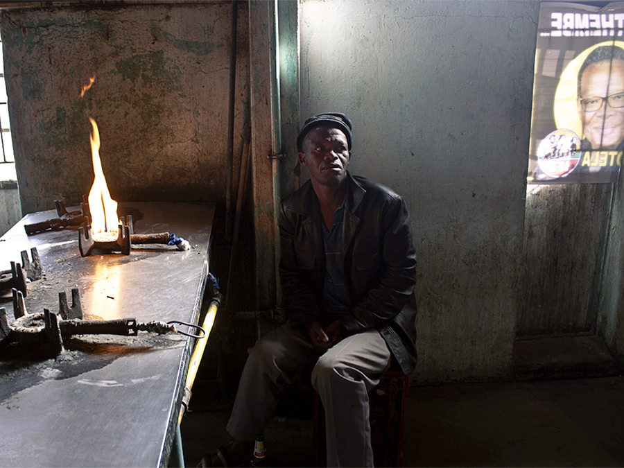 MDA_20200630_07 – Alexandra, Johannesburg. Bongomusa Mdletshe (58) is  using a gas stove to fight the cold in the cement kitchen of the hostel. ©Manash Das.