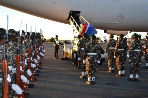 One of two caskets draped with a Namibian flag, each containing ten human skulls, is taken from an airplane on October 4, 2011, in Windhoek. They were the skulls of Herero and Nama genocide victims taken to Germany more than a century before. (Brigitte Weidlich/AFP)
