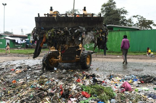 A man walks past a excavator moving a heap of garbage into a truck in the suburb of Shauri Moyo, in Nairobi, on November 25, 2019. SIMON MAINA / AFP