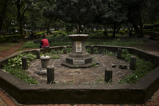 A man rests on the octagon surrounding the destroyed plinth upon which a colonial era statue of H.M. Queen Victoria had stood in memoria since it's unveiling in 1906, at the Jevanjee gardens in Nairobi on June 13, 2020. The statue was removed following a vandalism incident a few years ago.  Statues of controversial historical and political figures are under scrutiny worldwide. TONY KARUMBA / AFP