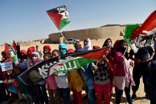 Sahrawi refugee children welcome the new UN envoy for the disputed territory of Western Sahara to the Aousserd camp for Sahrawi refugees on the outskirts of Tindouf on October 18, 2017.  RYAD KRAMDI / AFP