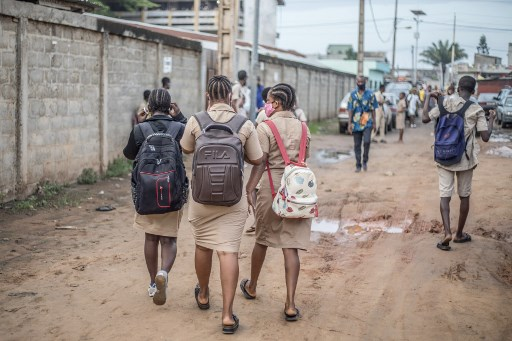 Students walk towards the General Education College (CEG) in Godomey, as school resumes on May 11, 2020. Schools in Benin reopened on Monday, with strict instructions on distance, hygiene and distribution of masks, after several weeks of closure to curb the spread of the new coronavirus.