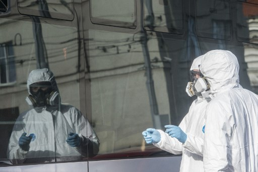 Two workers stand next to a tram during a test of new nano polymer disinfection as part of precautionary measures against the spread of the new coronavirus COVID-19