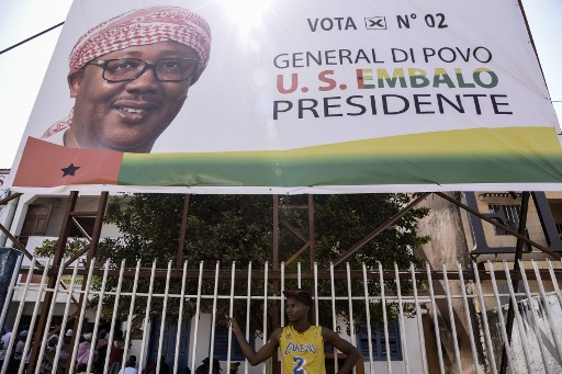 A man stands in front of a sign of opposition Presidential candidate Umaro Sissoco Embalo in Bissau, on December 27, 2019, ahead of the second round of the presidential elections. Voters in Guinea-Bissau are being called out to cast their ballots in a presidential runoff on December 29, capping a year of turmoil in the poor, coup-prone West African state. After months of acrimony, people are being asked to choose between two former prime ministers -- Domingos Simoes Pereira, from the traditional ruling PAIGC party, and opposition figure Umaro Sissoco Embalo. SEYLLOU / AFP