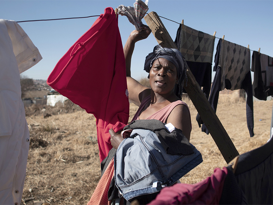 XPA_20200630_01 – Soweto, Johannesburg. A woman hanging her laundry in the hostel's backyard. ©Alessandro Parodi.