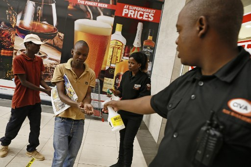 Security officials sprays disinfectant on a shopper's hands as part of an intervention by Mams Mall Centre Management to counter the spread of the COVID-19 coronavirus in Mamelodi, near Pretoria, on March 29, 2020. South Africa came under a nationwide lockdown on March 27, 2020, joining other African countries imposing strict curfews and shutdowns in an attempt to halt the spread of the COVID-19 coronavirus across the continent. Phill Magakoe / AFP